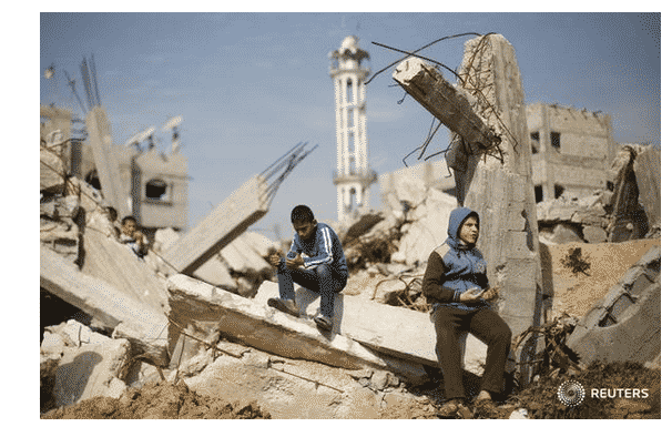 Muslim boys praying in ruins