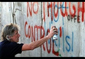 Roger Waters spray painting on separation barrier wall