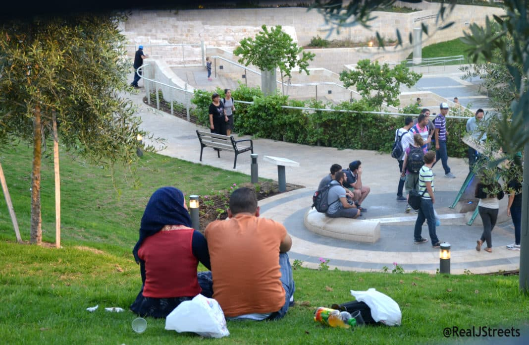 Muslim amn and woman sit in Teddy Park Jerusalem
