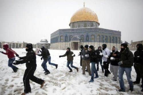 Palestinians play with snow outside the Dome of the Rock at the Al-Aqsa mosque compound in Jerusalem on January 10, 2013